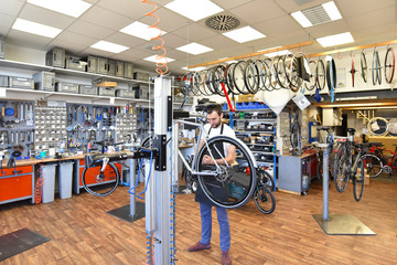 friendly and competent bicycle mechanic in a workshop repairs a bike Wall mural