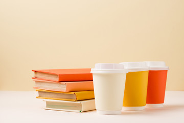 stack of books and colorful disposable cups on white surface isolated on beige