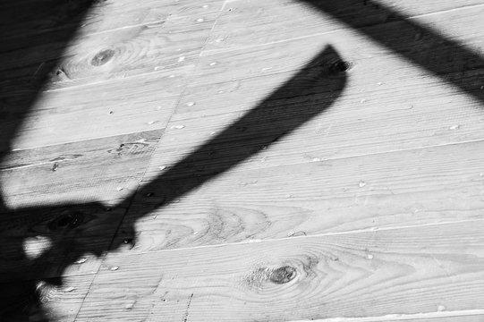 a shadow of a hand holding bid machete knife