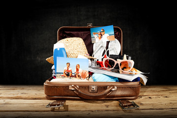 Summer suitcase and dark background of free space for your decoration.