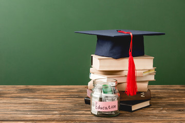books, academic cap and piggy bank on wooden surface isolated on green