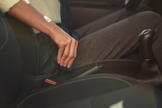 Woman is fastening safety seat belt in the car