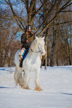 Man in suit of ancient warrior riding big white horse
