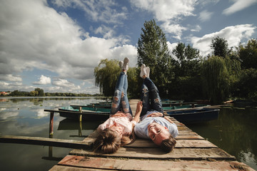 Perfect date. Beautiful young couple and smiling while lying on the pier. happy young man and woman laughing while lying on wooden pier near water Wall mural