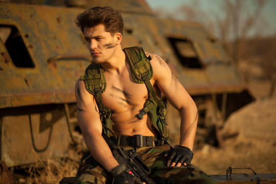 Strong military man with weapon looking aside thoughtfully,beside the abandoned tank.Horizontal view