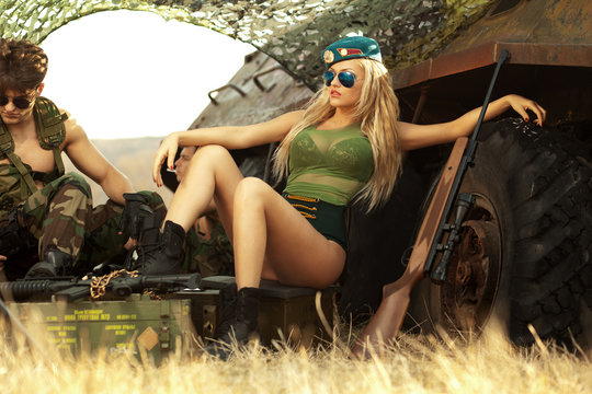 Sexy blonde woman in hot clothing poses with attitude near military tank, near hot, muscular brunette soldier, in danger places.