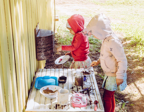 Two young girls sisters play outdoors in so called mud kitchen, where you can make fake food, play with sand, dirt, water, plants and make a mess it develops imagination and exploration.
