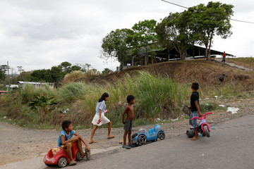 Children play on in plastic cars on the street of a low-income neighbourhood in Panama City