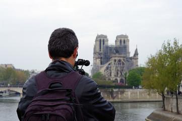 Homme prenant en photo l'arrière de Notre-Dame