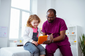 Pediatrician showing cartoon on tablet for his little patient