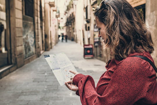 Barcelona, beautiful woman tourist with map on the street