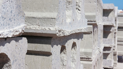 Close-up on a stack of concrete slabs or hollow concrete blocks, one of the raw materials used in roads or house building. Precast cement based blocks, used as structural material in construction.