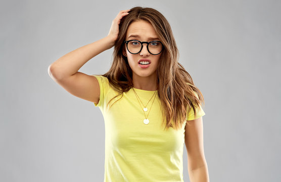 people, emotion and expression concept - confused young woman or teenage girl in yellow t-shirt and glasses over grey background
