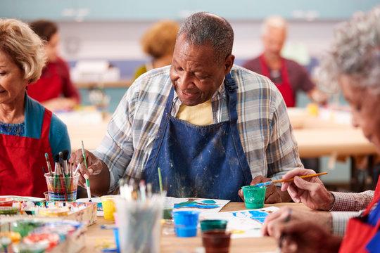 Retired Senior Man Attending Art Class In Community Centre