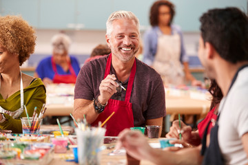 Group Of Mature Adults Attending Art Class In Community Centre