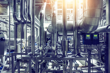 Stainless steel pipes and pipelines in modern beer factory. Brewery production equipment, abstract industrial background in blue color with light effect,