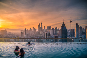 Traveler looking view skyline Kuala Lumpur city in swimming pool on the roof top of hotel at sunrise in Kuala Lumpur, Malaysia.