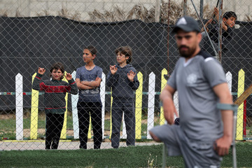 Children standing by a fence watch Palestinian amputees playing a soccer match as part of an initiative organised by the Palestinian Youths Council, in Khan Younis in the southern Gaza Strip