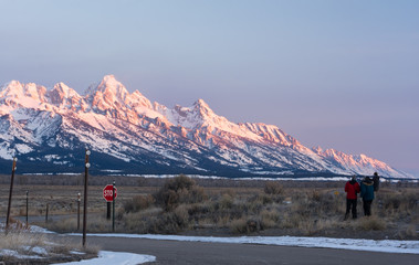 Wearing thick jackets a group of people watch the pink light of sunrise slide down the east slope of the Grand Tetons