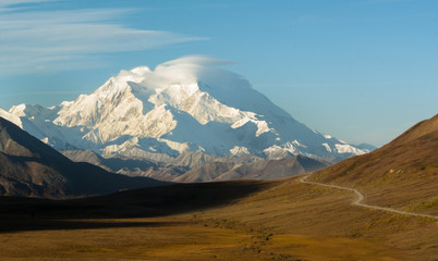 Strong winds shape the clouds over Mt Denali the highest mountain in North America as seen across a u shaped valley with a dirt road running along the north slope
