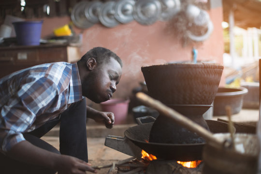 African man sitting to blow fire to cook rice