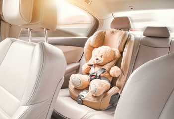 Baby child seat car. A beige teddy bear is fastened with seat belts in a car seat. Travel by car