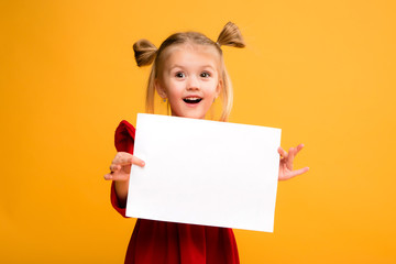 baby girl holding white sheet.Cute little girl with white sheet of paper.yellow background.copy spase.Little girl holding empty sheet of a paper Wall mural