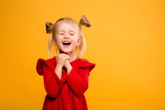 baby girl portrait isolate yellow background.Stylish little baby with hands up. Portrait of shocked little girl in red dress isolated on yellow background