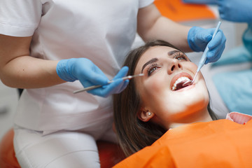 Dental clinic. Reception, examination of the patient. Teeth care. Young woman undergoes a dental examination by a dentist.Happy patient and dentist concept.Female dentist in dental office talking with