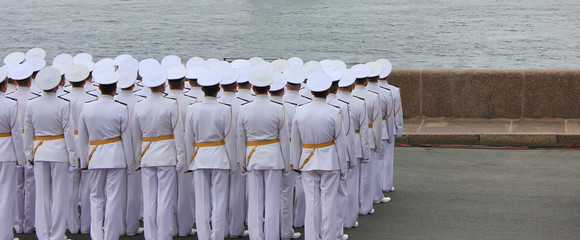 Naval officers backside view standing together in group at military parade rehearsal in St. Petersburg, Russia