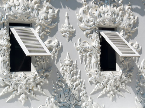 White temple, Wat Rong Khun in Chiang Rai. Detail of a wall with opened windows and decorations as leaves .