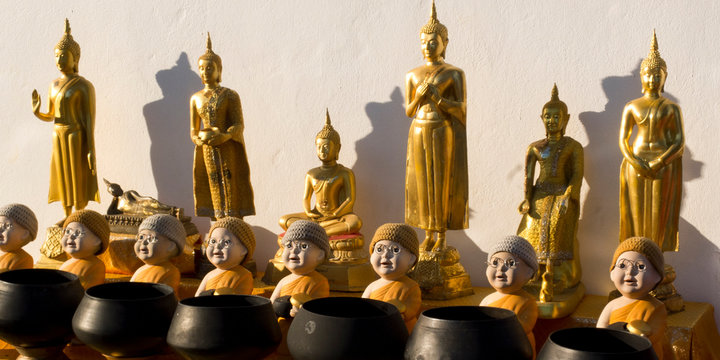 Golden-coloured Buddhas in several postures : standing, sitting, and monk dolls before their charity bowls.