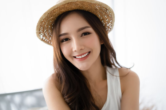 Portrait of a woman in a hat, closeup portrait of a nice female in summer straw hat and looking at camera.Concept woman lifestyle,happy healthy summer vacation.