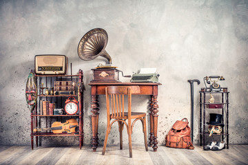 Foto op Canvas Retro Antique chair, old typewriter, retro radio, gramophone on wooden desk, books, clock, camera, binoculars, fiddle, keys on shelf, mask, cylinder hat, shoes, cane, backpack. Vintage style filtered photo