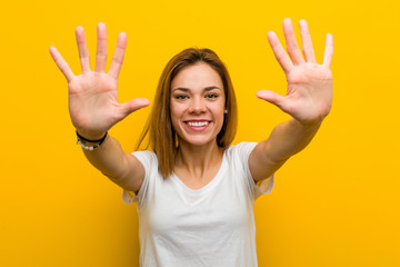 Young natural caucasian woman showing number ten with hands.
