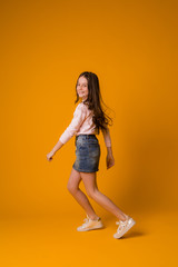 kid girl jumping happy girl dancing on yellow background