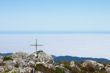 A wooden cross on top of Formosa mountain peak near Plettenberg Bay, South Africa. Christianity religion concept image.