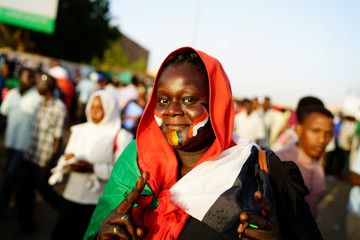 A Sudanese protester makes a victory sign as she attends a demonstration in front of the defense ministry compound in Khartoum