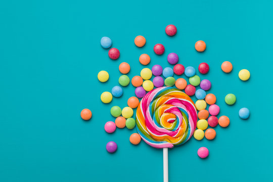 Sweet lollipop and colorful chocolate candy pills.