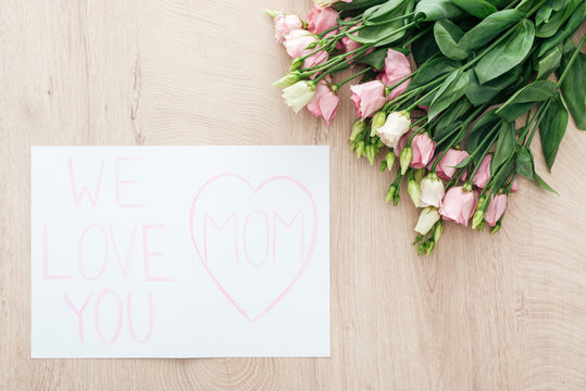 top view of eustoma flowers and card with we love you mom greeting on wooden table