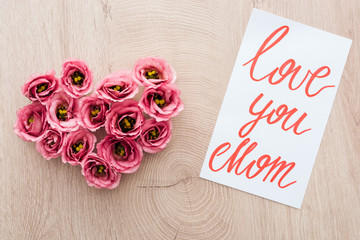 top view of heart sign made of eustoma flowers and card with love you mom lettering on wooden table