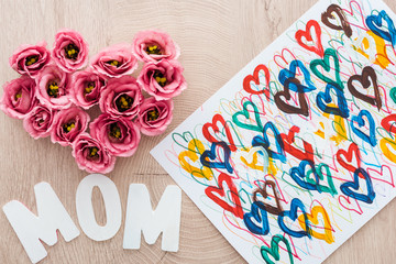 top view of heart sign made of eustoma flowers, drawing and mom sign on wooden table