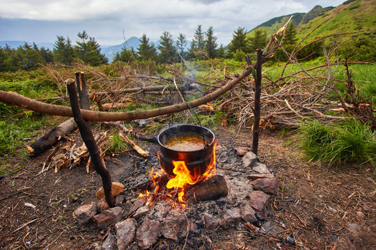 Old small kettle is heated on a bonfire on a green mountain meadow during a bad weather.