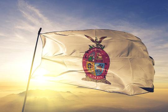 Sinaloa state of Mexico flag waving on the top sunrise mist fog
