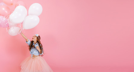 Pretty little girl with long curly hair, in pink tulle skirt having fun with flying above balloons isolated on pink background. Happy childhood of amazing kid expressing positivity. Place for text