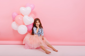 Amazing happy moments of young cute charming little girl with long brunette hair sitting on big present with flying balloons isolated on pink background. Expressing true emotions. Place for text