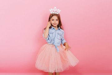 Cheerful little girl with long brunette hair in tulle skirt holding princess crown on head  isolated on pink background. Celebrating brightful carnival for kids, birthday party, having fun of cute kid Wall mural