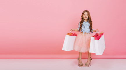 Happy lovely moments of shopping time with cute little girl in tulle skirt standing in mothers big shoes with white packages in hands isolated on pink background. Place for text