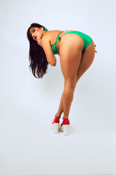 Hispanic woman in green bikini poses against a white background