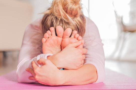 Woman practicing yoga, seated forward bend pose, doing paschimottanasana exercise